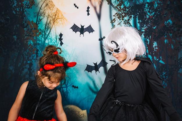 Les filles en costumes d'halloween regardent vers le bas