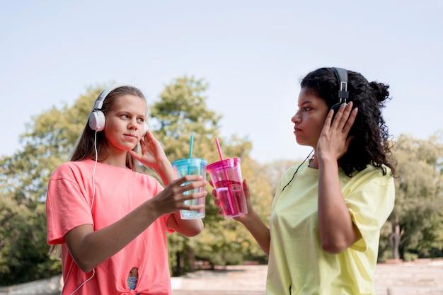 Filles coup moyen écoutant de la musique