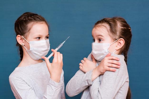 Les filles dans des masques médicaux regardent une seringue avec des médicaments à la main. vaccination, traitement des enfants. prévention des épidémies