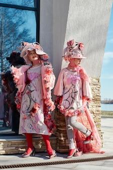 Filles dans de nouveaux vêtements créatifs de mode vogue posant dans la rue, robe rose et chapeau, vêtements ethniques