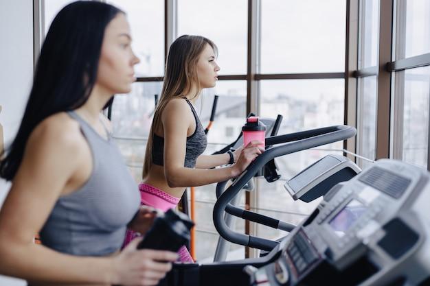 Les filles dans la salle de gym sont formés sur des tapis roulants et boivent de l'eau, souriant
