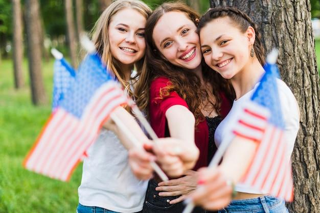 Filles devant l'arbre avec des drapeaux américains
