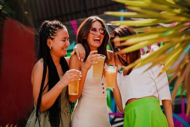 Les filles discutent et boivent des cocktails sur la terrasse d'été, photo de style de vie