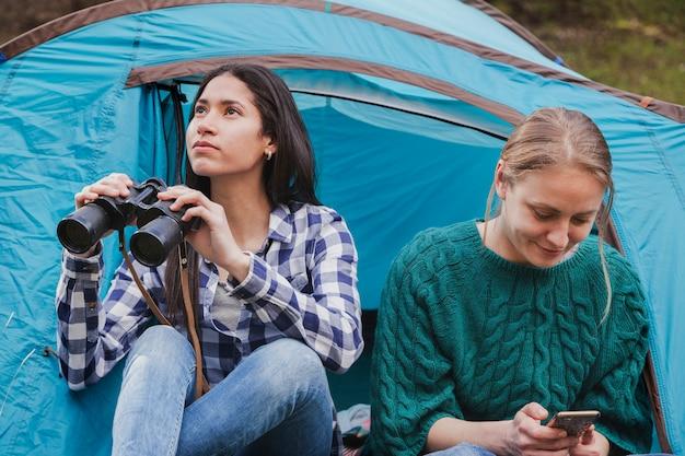 Des filles distraits avec des jumelles et un téléphone mobile