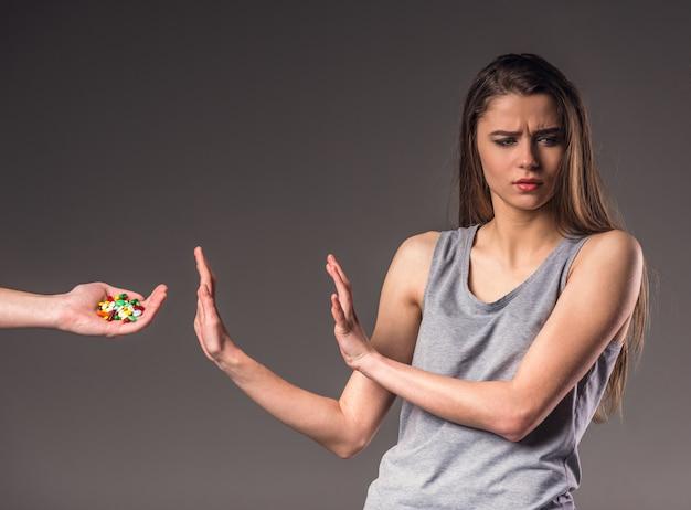 Les filles donnent des pilules et elle les refuse.