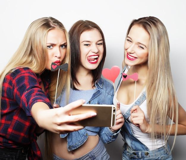 Filles drôles prêtes pour la fête et prenant un selfie