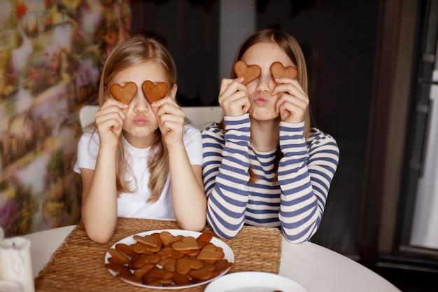 Des filles drôles et rieuses tiennent des biscuits en forme de cœur, ferment les yeux et s'amusent