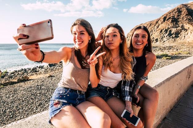 Filles du millénaire prenant une photo de selfie avec un téléphone moderne pour les médias sociaux s'amusant beaucoup ensemble dans l'amitié