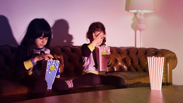 Filles avec du pop-corn sur le canapé