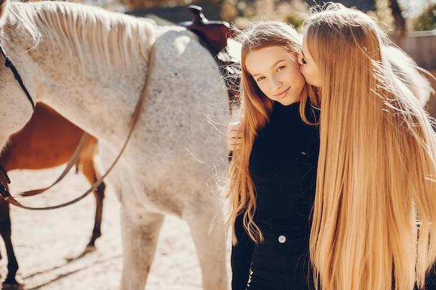 Filles élégantes avec un cheval dans un ranch