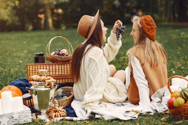 Filles élégantes et élégantes, assis dans un parc en automne