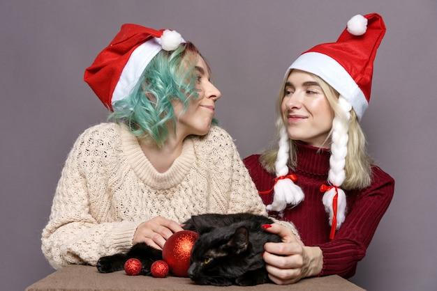 Filles élégantes et heureuses dans la casquette du nouvel an joue avec un joli chat noir sur fond gris jeune hipster ...