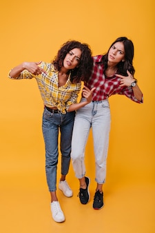 Les filles émotionnelles et mécontentes regardent avec défi. portrait de brunes frisées dans des chemises multicolores.