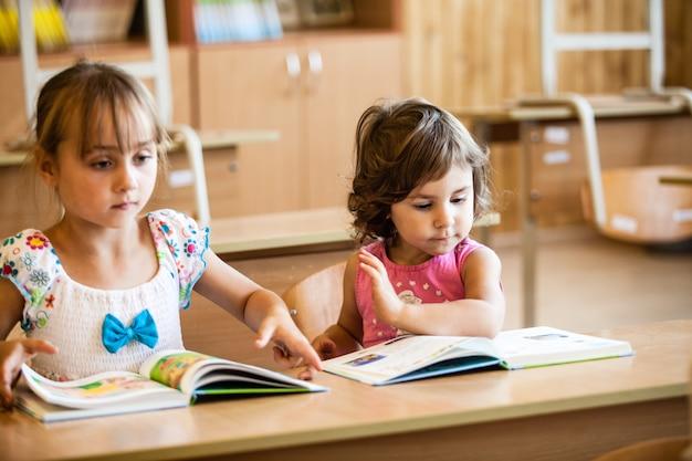 Les filles étudient à l'école maternelle au bureau