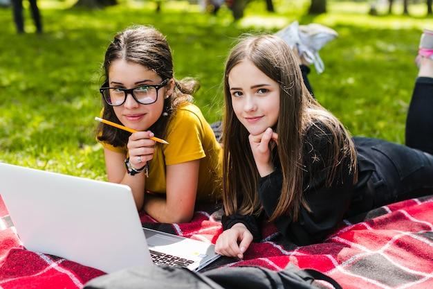 Les filles étudient et posent sur l'herbe