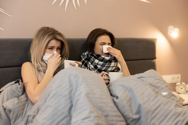 Filles européennes malsaines allongées sur le lit sous des couvertures et éternuant dans des mouchoirs en papier. les jeunes femmes portent des foulards et tiennent des tasses avec du thé chaud. intérieur de chambre à coucher dans l'appartement moderne