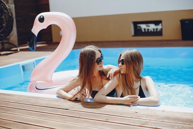 Filles à la fête de l'été dans la piscine
