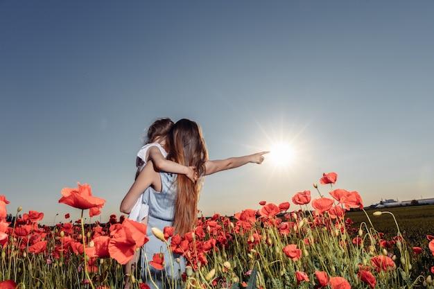 Filles filles avec maman dans un champ de coquelicots. le concept de tendresse. famille heureuse. champ de coquelicots rouges.
