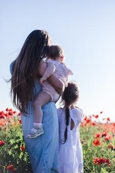 Filles filles avec maman dans un champ de coquelicots. la notion de tendresse. famille. champ de coquelicots rouges.