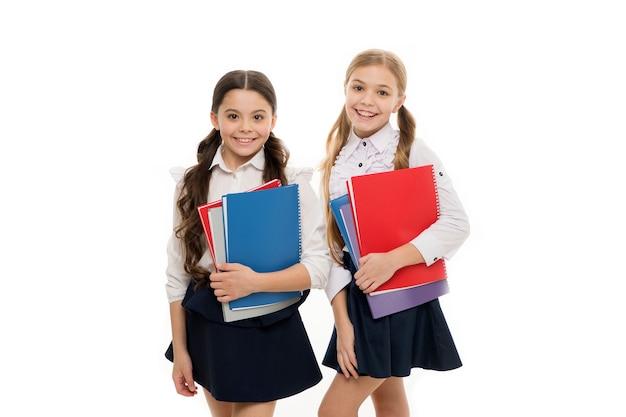 Filles avec fond blanc de manuels scolaires. nous aimons étudier. étudier est amusant. acheter un livre pour un cours extrascolaire. notion d'école. les élèves transportent des manuels dans les classes de l'école. cours de langue pour les jeunes.