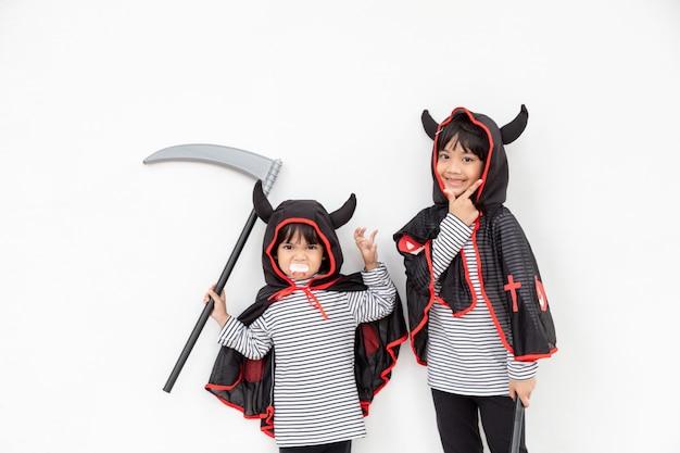Filles fraternelles heureuses à la fête d'halloween. enfants portant des costumes halloweens. concept d'enfants prêts pour une fête.
