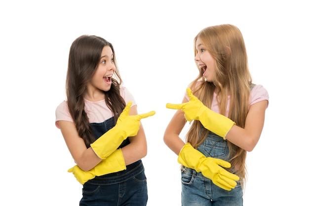Filles avec des gants de protection en caoutchouc jaune prêts pour le nettoyage. tâches ménagères. petite aide. les filles mignonnes adorent nettoyer. garde le propre. protège les peaux sensibles. les enfants nettoient ensemble.