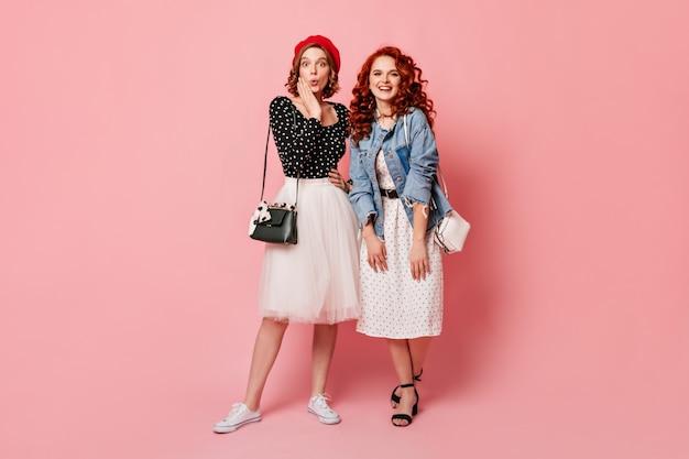 Filles glamour surpris regardant la caméra avec le sourire. photo de studio de jolies amies posant sur fond rose.