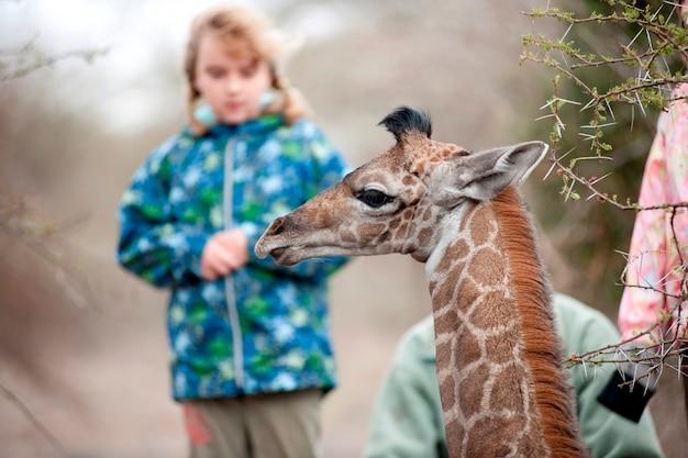 Filles avec guide et girafe