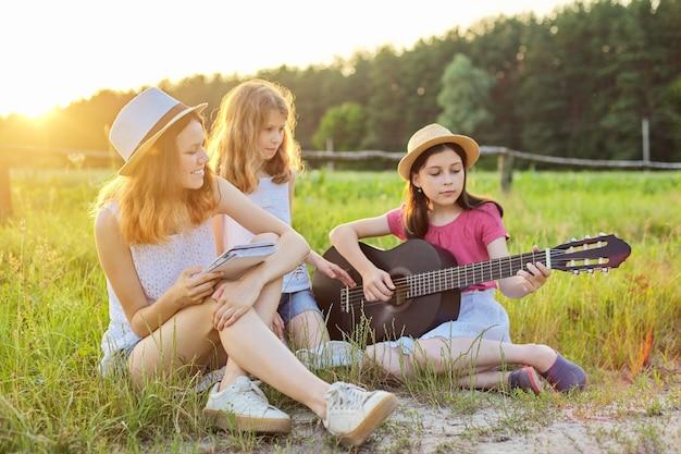 Filles avec guitare classique sur la nature