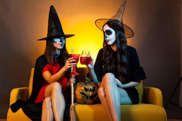 Les filles de halloween au canapé avec des boissons