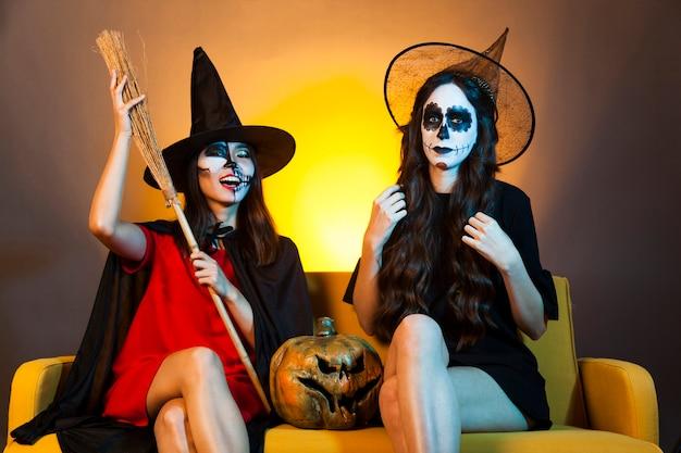 Filles d'halloween au canapé à la citrouille et au balai