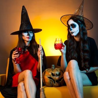 Les filles d'halloween au canapé avec de la citrouille et des boissons