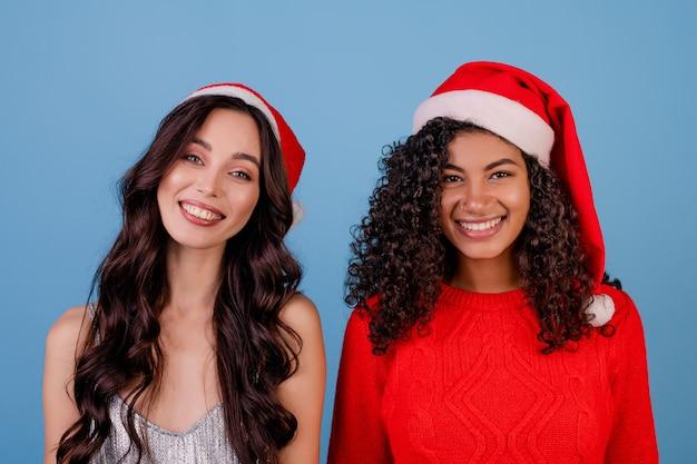 Filles heureuse portant des chapeaux de noël isolés sur bleu
