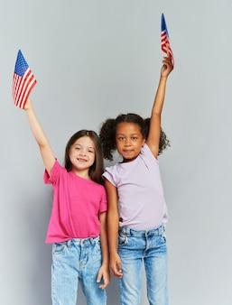 Filles heureuses agitant des drapeaux américains