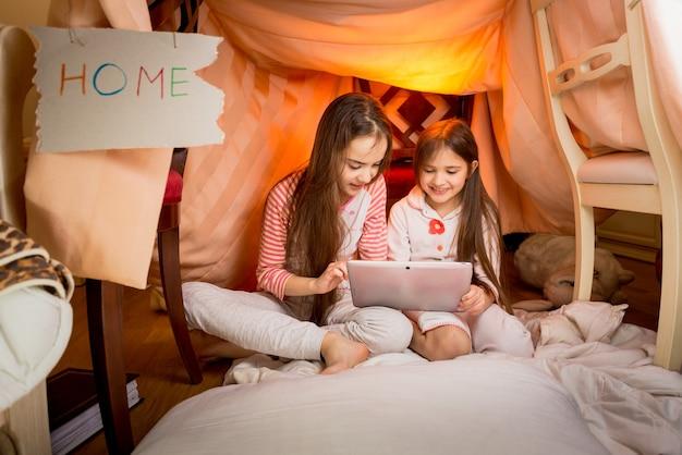 Filles heureuses assises dans une maison faite de couvertures et utilisant une tablette numérique