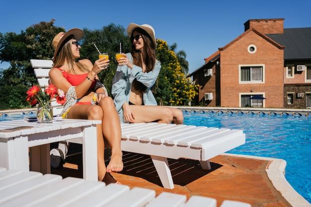 Filles heureuses avec des boissons s'amusant près d'une piscine d'hôtel.