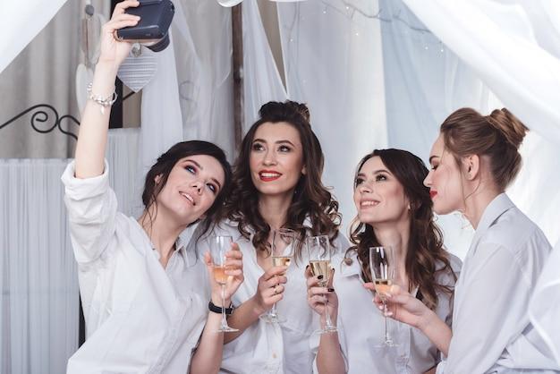 Filles heureuses en chemises d'hommes blancs qui célèbrent une fête de célibataire