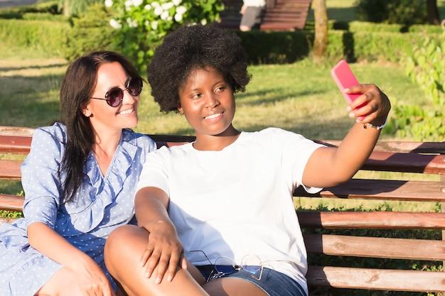 Des filles heureuses de différentes nationalités prennent des selfies en été.