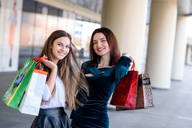 Filles heureuses souriant et faisant des courses dans le centre commercial.