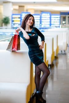 Filles heureuses souriantes et faire du shopping dans le centre commercial.
