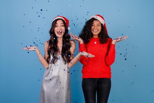 Filles heureux avec des confettis dans l'air portant des chapeaux de noël isolés sur bleu