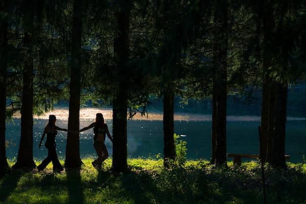 Filles hippies assez libres marchant dans les bois. vue sur le lac - photo effet vintage