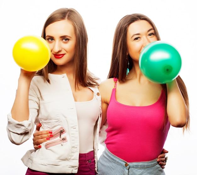 Filles de hipster souriant et tenant des ballons colorés