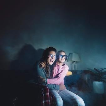 Filles hurlantes effrayées devant la télé
