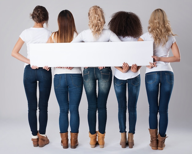Filles en jeans tenant une bannière vide