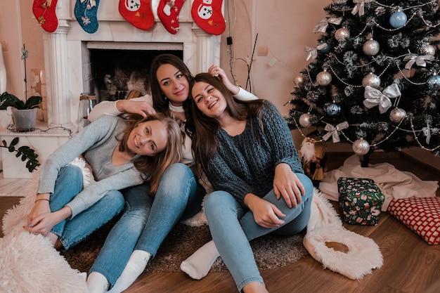 Filles de jeune femme d'arbre s'asseyant à côté de la cheminée et de l'arbre de noël. s'amuser, convivialité et amitié. le pouvoir des filles. célébration du nouvel an. des journées d'hiver agréables. home sweet home.