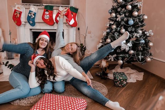 Filles de jeune femme d'arbre s'asseyant à côté de la cheminée et de l'arbre de noël. s'amuser, convivialité et amitié. le pouvoir des filles. célébration du nouvel an.