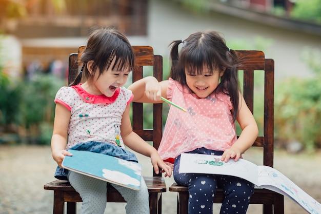 Filles jouant avec des livres à colorier