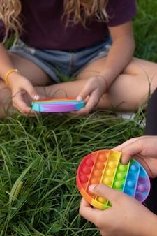 Les filles jouent au jouet pop-it populaire en silicone coloré à l'extérieur sur l'herbe verte