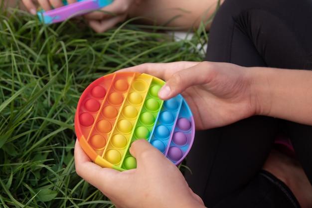 Les filles jouent au jouet popit populaire en silicone coloré à l'extérieur sur l'herbe verte